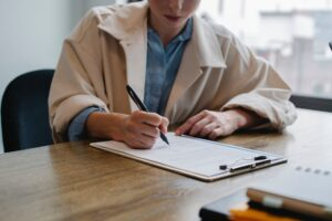 focused woman writing in clipboard while hiring candidate